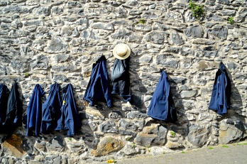 Coats from the toboggan drivers hanging on a wall near their top station, Funchal, Madeira