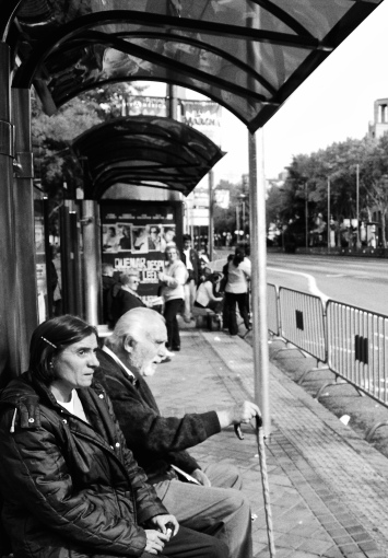 Couple waiting at a bus stop during National Day celebrations