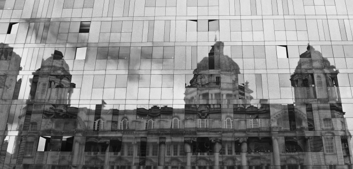 The Port of Liverpool building reflected in the modern black glass Mann Island building.