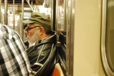 A man has a nap whilst on a subway train.