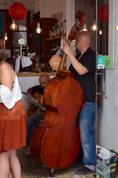 Jazz musicians entertain cafe patrons and passers-by