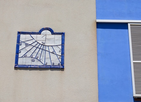 A sundial on the side of a row of houses