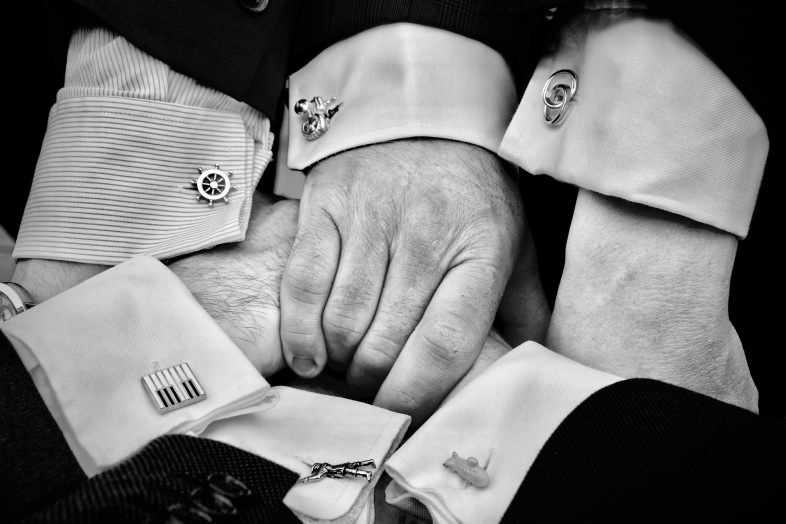 Image displays six men's hands with shirts and cufflinks